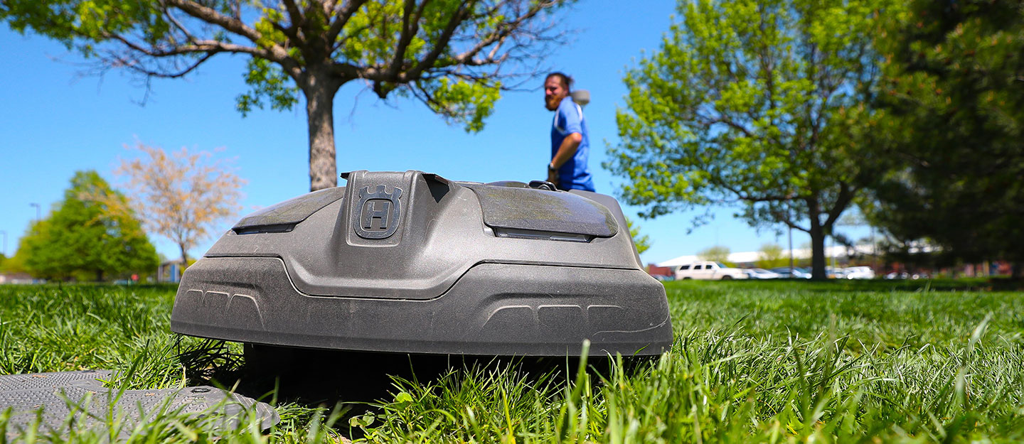 A robotic mower cuts grass at the marching band practice field between the College of Education building and West Center on the UNK campus