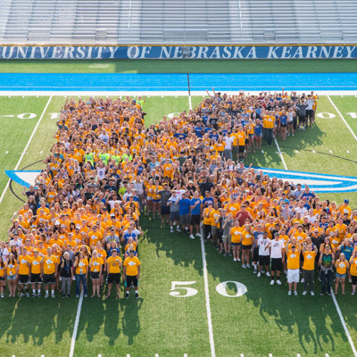UNK students on football field in K formation