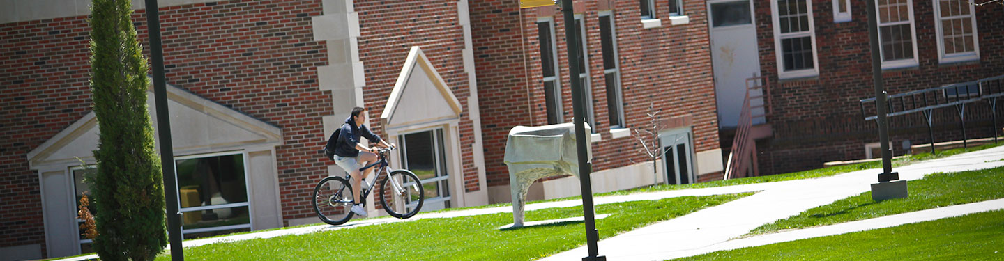 Student on Bike in front of West Center